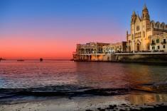 Malta - Vacker solnedgång med röd himmel vid St Julians Bay