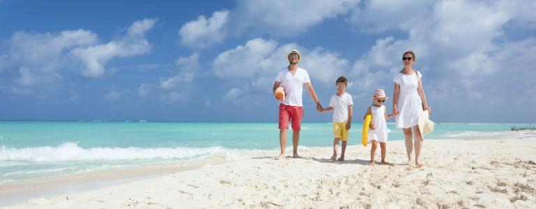 En familj går på en sandstrand 768x300
