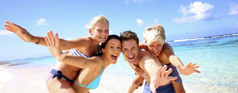 Glad familj på en strand 768x300